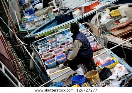 HONG KONG, CHINA - JAN 27: Local fishman selling their fish on Jan 27, 2013 in Sai Kung, Hong Kong. They selling fish directly on boat and use their fishing net to give the fish to the customer.