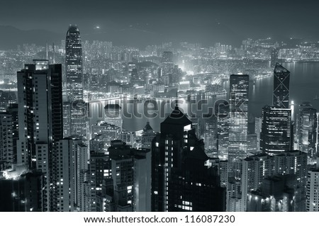 Hong Kong city skyline at night with Victoria Harbor and skyscrapers illuminated by lights over water viewed from mountain top in black and white. - stock photo