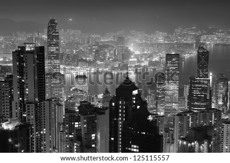 Hong Kong city skyline at night with Victoria Harbor and skyscrapers illuminated by lights over water viewed from mountain top in black and white.