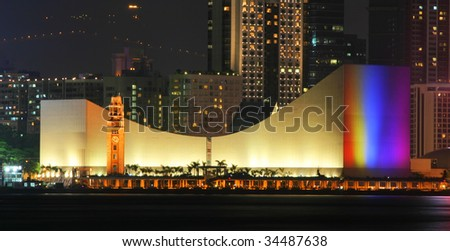 Hong Kong Cultural Centre with colorful light projection on its wall.