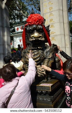HONG KONG - JANUARY 23, 2017: The crowd of faithfulness chinese people try to touch on the part of body of Kirin statue for their believe in lucky and healthy to release from their body painful #563508112