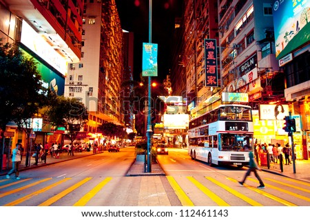 HONG KONG - JULY 30, 2012: signs, people and tram on Nathan Road in Kowloon, Hong Kong on July 30, 2012. Nathan Road is the main thoroughfare in Kowloon and is lined with shops and restaurants. - stock photo
