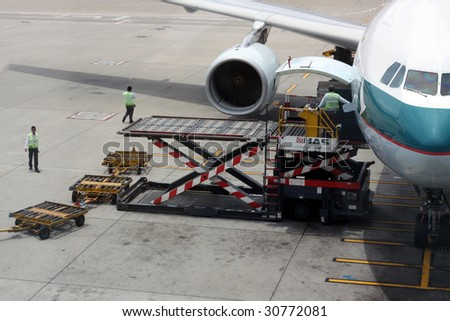 HONG KONG - MAY 16: Cathay aircraft being unloaded at Hong Kong airport on May 16, 2009 in Hong Kong. Aside from China Airlines, Cathay is one of the most busy carriers in the region.