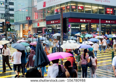 HONG KONG - MAY 20: People in the rain on May 20, 2012 in Hong Kong. With a land mass of 1,104 km and population of 7 million people, Hong Kong is one of the most densely populated areas in the world