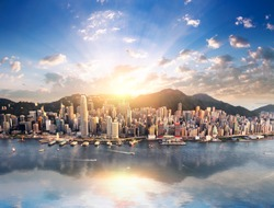 Hong Kong skyline. Hongkong hdr aerial cityscape with sunset sun. Amazing panorama of buildings and sky reflecting in harbour