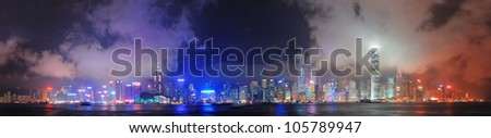 Hong Kong skyline panorama at night with clouds over Victoria Harbour.