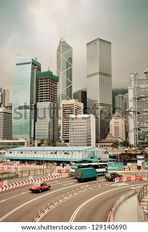 Hong Kong street view with traffic and skyscrapers.