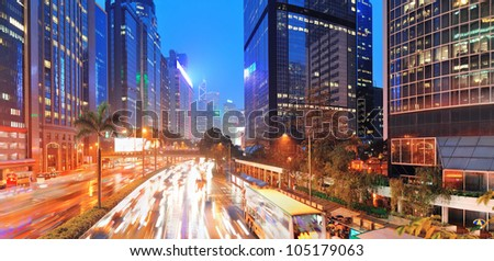 Hong Kong street with busy traffic and skyscraper office at dusk.