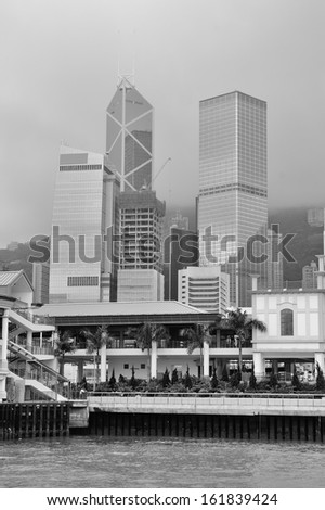 Hong Kong urban architecture over sea with skyscrapers in black and white.