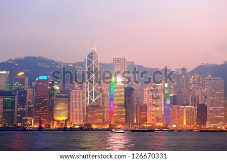 Hong Kong Victoria Harbor morning with urban skyscrapers over sea lit with reflections.