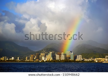 Honolulu Hawaii with a bright rainbow after a rain storm seen from the open ocean on Oahu island