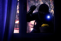Hooded burglar forcing the window frame - Silhouette of thief with screwdriver and flashlight is breaking into the apartment - Concept of intrusion and danger view from indoor dark shaded image