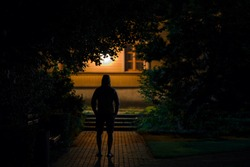 Hooded man standing on sidewalk at dark park in summer black night. Scary moment and gloomy atmosphere. Thief watching house. Back view.