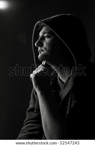 Hooded man sticking a razorblade to his neck
