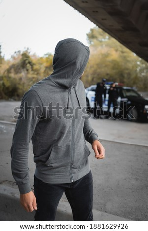 hooded thief looking away with blurred multicultural police officers on background outdoors Foto stock ©