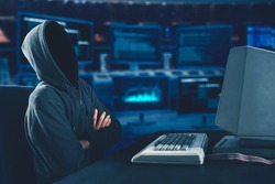 Hooded unknown hacker looks thinking with computer on desk and coding background