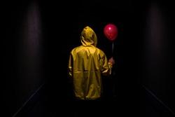 Hooded yellow figure with red balloon in dark creepy corridor