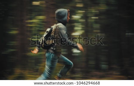 Hooded young man with backpack running in the forest
