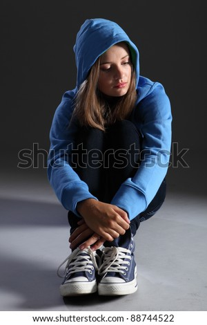 Hoodie on for distressed and frightened young blonde teenager girl sitting on floor looking scared and alone with big sad eyes, wearing jeans and blue jumper.