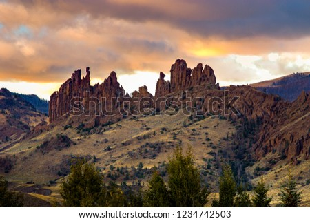 Hoodoos in Wyoming in the sunrise light with colorful clouds above and rolling green hills in the foreground. The area of Wapiti has geological formations throughout the valley. #1234742503