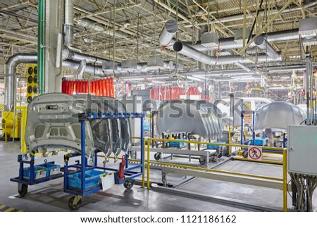 Hoods for cars in a row of silvery color unpainted. Machine parts. The warehouse of the automobile factory.