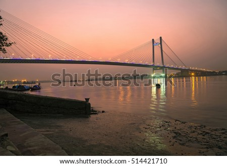 Hooghly river bridge at twilight. The hooghly river bridge known as the Vidyasagar Setu is the longest cable stayed bridge in India connecting Kolkata with the Howrah district. #514421710
