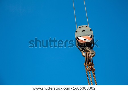 Hook bottle of a crane with ropes, eyelets, link chain and hook against a blue sky. The equipment is used for lifting heavy loads