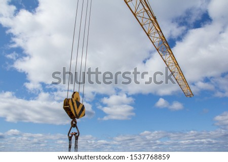 Hook of a large construction crane against the blue sky. Part of the mechanism for lifting heavy loads at a construction site #1537768859