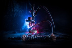 Hookah hot coals on shisha bowl on dark foggy background. Stylish oriental shisha. Creative concept