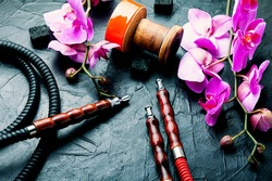 Hookah mouthpiece and hookah cup on pink orchid background.Kalian on flower tobacco