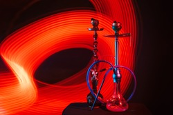 hookahs with hot shisha charcoals in bowls on the table on a dark background with red neon glow
