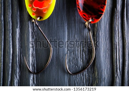 Hooks for trout baits. Spoon baits close-up on black wooden background. Colorful fishing baits. #1356173219