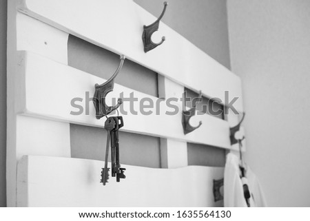 Hooks on hooks on white wall with boards. Home furnishings with a symbol of home and warmth - keys to the apartment or heart.