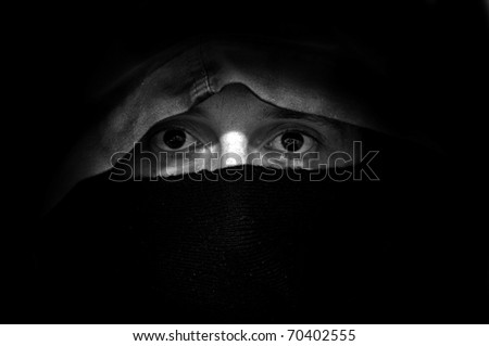 Hooligan under hood, close up image of man's eyes.