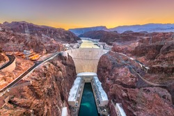 Hoover Dam on the Colorado River straddling Nevada and Arizona at dawn from above.