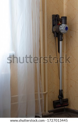 Hoover, vacuum cleaner charging in the home near the window. Sweet home concept. Keep clean Stock photo ©
