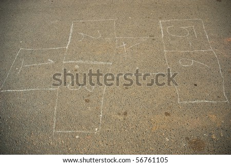 Hop scotch game drawn out on a road surface with white crayon