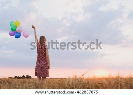 hope concept, emotions and feelings, woman with colorful balloons in the field, background
