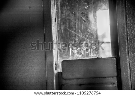 Hope etched into window of solitary confinement cell metal door inside old prison. #1105276754