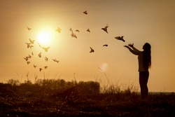 Hope faith concept. Woman launches doves on the background of a sunny sunset.