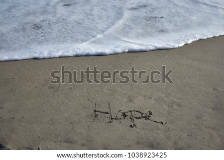 Hope Inscribed on the Beach in front of an Approaching Wave #1038923425