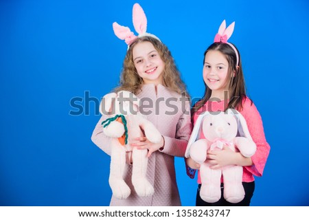 Hope love and joyful living. Friends little girls with bunny ears celebrate Easter. Children with bunny toys on blue background. Sisters smiling cute bunny costumes. Spread joy and happiness around. #1358243747