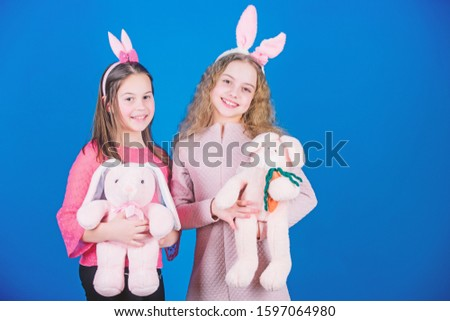 Hope love and joyful living. Friends little girls with bunny ears celebrate Easter. Children with bunny toys on blue background. Sisters smiling cute bunny costumes. Spread joy and happiness around.