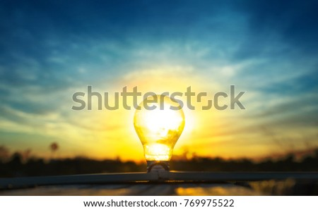 Hope of energy and idea concept, Light lamp with sunlight and sunset background