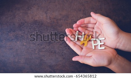 Hope with yellow gold ribbons on hands, Sarcoma Awareness, Bone cancer, Liver cancer, Bladder Cancer, childhood cancer awareness, pamoramic banner #654365812