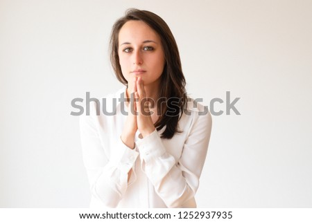 Hopeful office worker keeping palm together in please gesture. Beautiful young manager wishing success. Isolated on white. Praying gesture concept