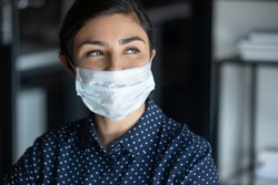 Hopeful smiling young woman in protective face mask look in distance hope for coronavirus pandemic end, happy millennial female in medical facial cover from COVID-19 thinking, healthcare concept