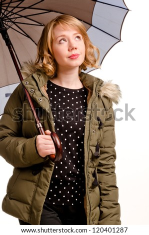 Hopeful young blonde woman checking out the weather as she stands under her umbrella looking up at the sky with a look of anticipation isolated on white