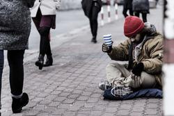 Hopeless beggar asking for food while sitting on the sidewalk between pedestrians