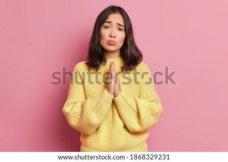 Hopeless brunette woman keeps palms pressed together and looks with imploring expression begs for favor asks to give one more chance wears long sleeved yellow jumper isolated over pink wall. Foto stock ©